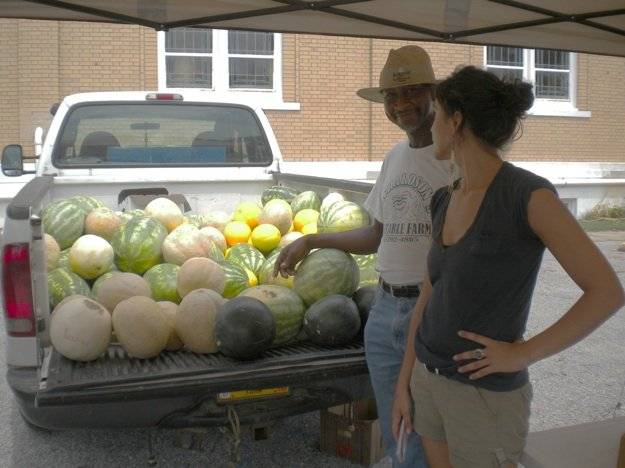 Market manager Debbi LaRue admires Steve Richardson's melon crop.
