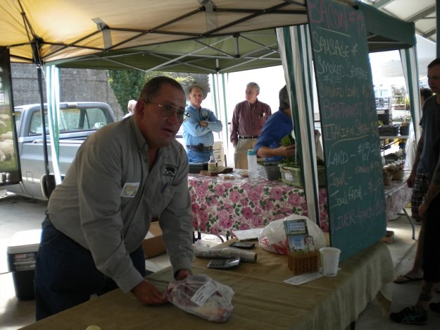 Mark Newman explains how to prepare a pork roast to a customer at the downtown market.