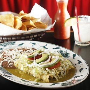 At Las Delicias, the popular Enchilada Verdes is smothered in tomatillo salsa and topped with sliced avocado.