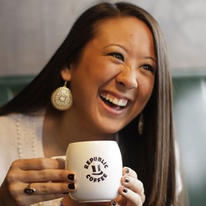 Ashley Sutherland enjoys a cup of fresh-brewed coffee and a laugh as teh mid-morning light streams in through the window at Republic Coffee.
