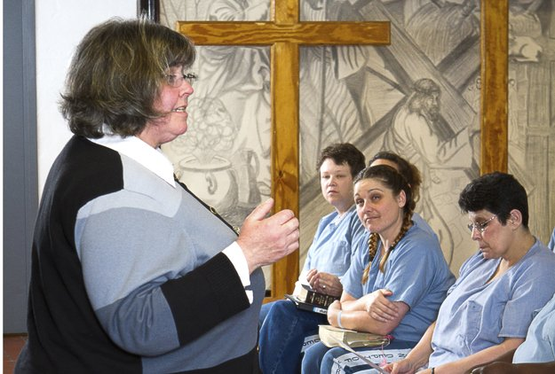 At Mark Luttrell Correctional Center, Reverend Diane Harrison leads inmates in worship.