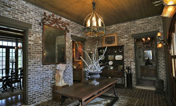 The rustic look of the brick reception room is offset by the elegant and sophisticated sculpture, mirror, and chandelier.