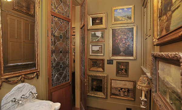 The powder room is a mini-museum with its floor-to-ceiling artworks, stained glass, and marble sink.