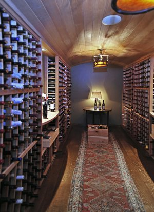 The wine cellar is warmed by a colorful runner and the glow from its handsome ceiling fixtures.