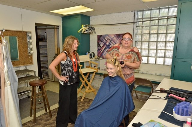Meg (seated) getting crimped by hair magicians, Alyx (L) and Mary (R).