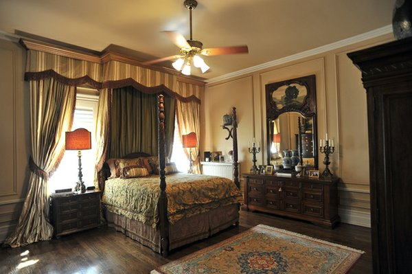 A partial view of the comfortable and luxe master suite with its handsome curtain and canopy configuration.
