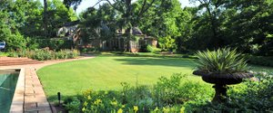 Sweeping vistas, such as this view looking across the sunny lawn to the rear of the home, are important features of this East Memphis garden.