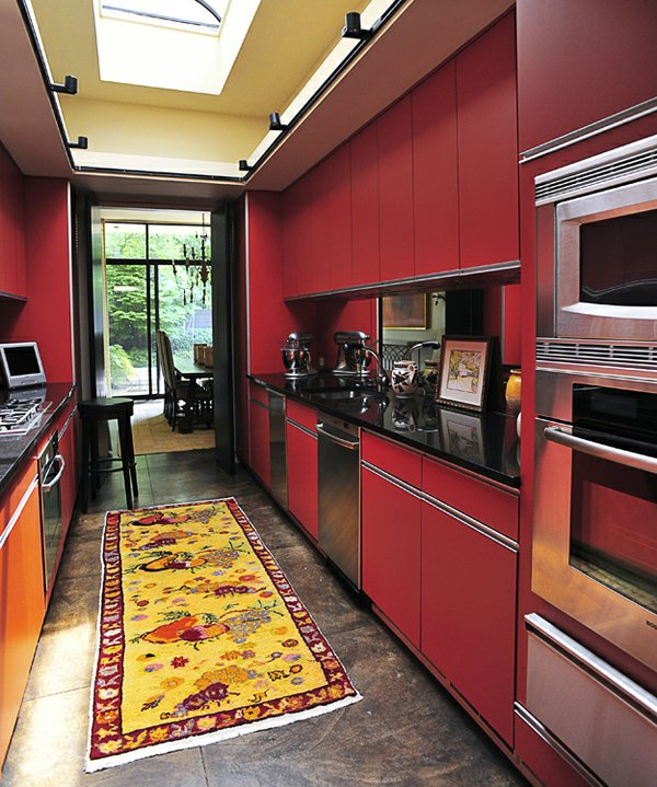 Chinese-red cabinets mesh beautifully with black countertops in the kitchen.