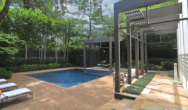 A stone terrace beckons visitors to a refreshing pool, making the Cooley home a true oasis in Central Gardens