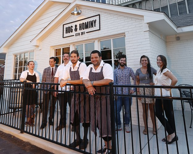 Andrew Ticer and Michael Hudman in front of Hog & Hominy with the establishment's management and culinary leaders.