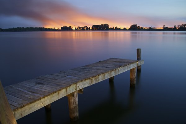 At first glance, this is a dramatic view of Horshoe Lake, with a magnificent sunset in the background. In reality, that golden glow is the result of fires set in the fall by farmers to clear away old crops and prepare for the new planting season. Fis...