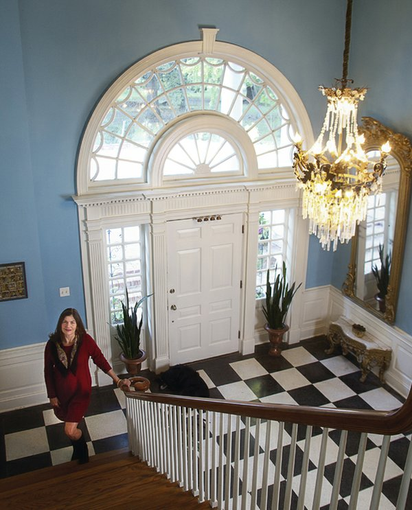 Martha McKay stands at the foot of the sweeping staircase in the Snowden House entry hall. This grand space didn't exist in the original house her grandfather built; it's one of the most impressive features of the 1949 renovation. The crystal chandel...