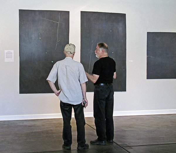 Robert McGowan (wearing cap) and Bert Sharpe prepare for the opening of the retrospective on South Main in October 2012. The show can be viewed by appointment through December.