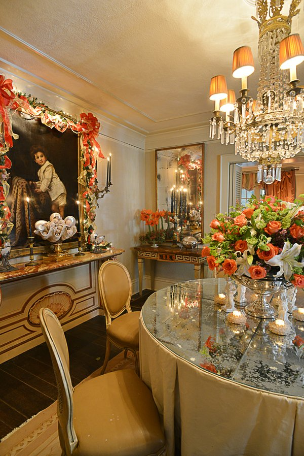 Candles, a crystal chandelier, and mirrored surfaces bathe the gorgeous dining room in a coral glow.