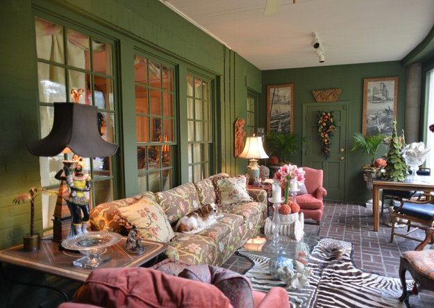 The Christmas-colored sunroom at the Moore home is an eclectic mix of architectural fragments, antique wallpaper panels, and a chintz-covered couch — all boldly anchored by a zebra rug.