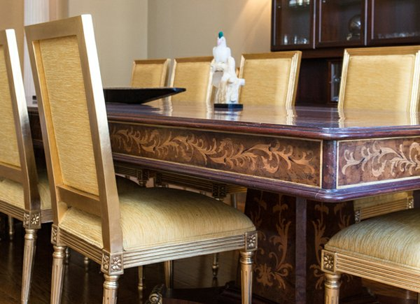 The marquetry work on the dining room table features carved veneer organic patterns inliad into the top and sides.
