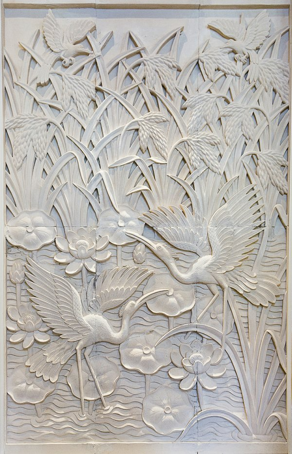 Also hand-carved in Bali by artisan Made, this sandstone wall depicts cranes wading in a pond flecked with lotus flowers.