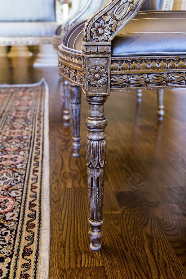 French artisan Jean Phillips spent two years hand-carving the intricate details of theses European-inspired teak chairs. The ornate legs are highlighted with gold leafing.