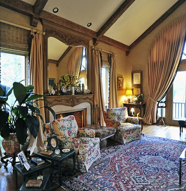 Distressed wooden beams add texture and rusticity to the gand living room with its elegant draperies and furnishings.