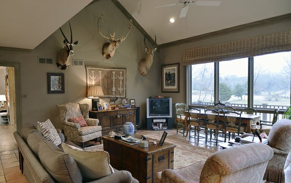 The comfortable family room offers wonderful outdoor vistas and displays three hunting trophies (gemsbok, caribou, and waterbuck).
