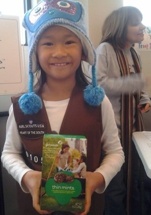 Ami Masler from Holy Rosary Troop 10105 shows off a box of Thin Mints.