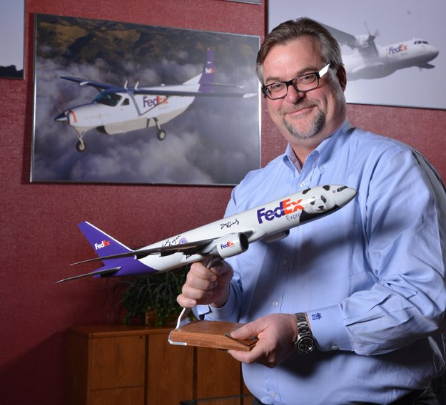 "David Lange holds a model of the special ""PandaExpress"" jet that carried pandas from China. The fuselage was autographed by members of the Panda Team."