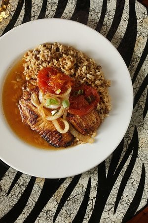 Kingston stew fish is a delicious blend of tilapia, pimentos, peppers and scallions served over rice and pigeon peas.