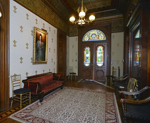 "Magnificent double doors with stained-glass panels open into the large entry hall which was intended to impress with its gold leaf fleur-de-lis patterned walls, expensive oriental carpet, and family portrait of ""Miss Daisy."""