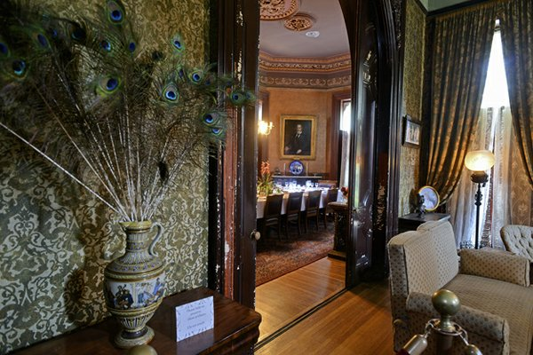 Looking from the small parlor/sitting room through a grand arch into the dining room with a vase of peacock feathers (an art nouveau flourish) in the foreground.