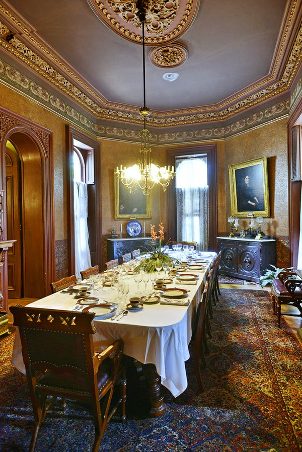 The dining room with its brown leather-covered chairs, richly colored carpet, and large table set for 12 is somewhat more masculine in feel than the other rooms in the house. It is said that the Victorians believed a calm, restful atmosphere in dark ...
