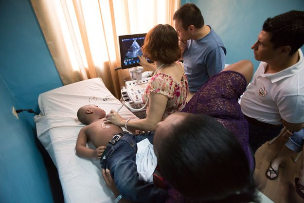 Juan Manuel Guity receives an echocardiogram while his motherlooks on.