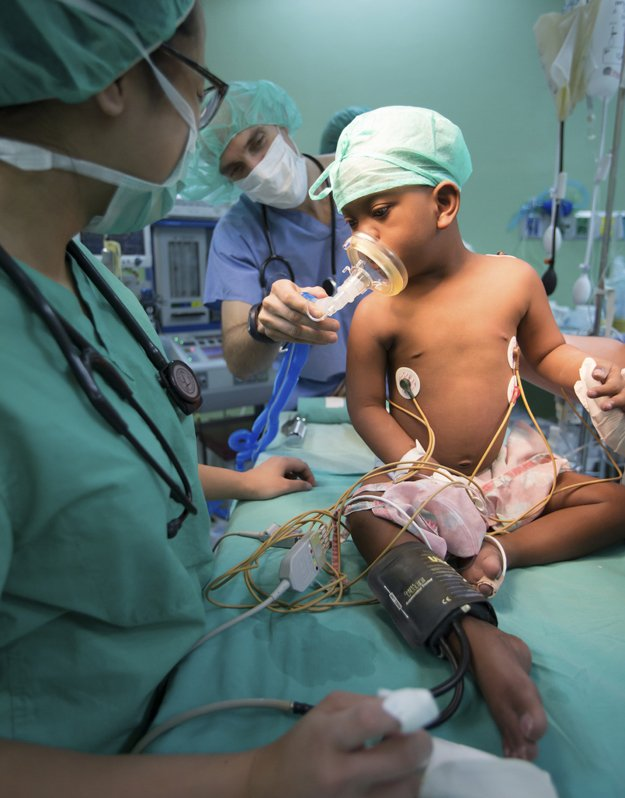 Juan Manuel receives oxygen from Dr. Juan Boriosi before an operation to correct a condition called Tetralogy of Fallot. This defect causes low oxygenation of the blood and bluish coloring. A shunt helped the child receive more blood flow to the lungs.