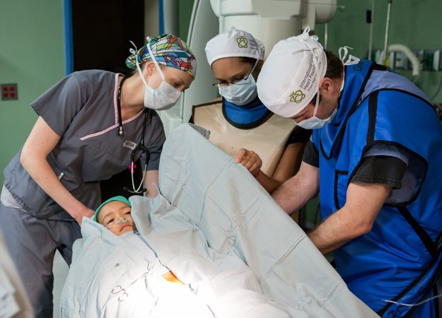 Registered nurse Randa Blenden, pre-med student Angelica Aguila, and cardiologist Dr. Jamie Penk prepare a  child for a diagnostic heart catheterization.