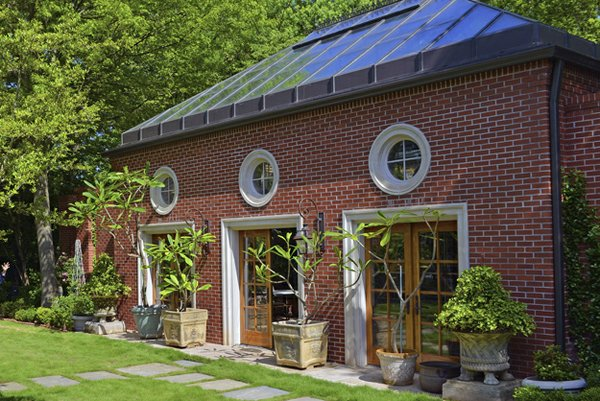 A variety of handpicked pottery and limestone planters frame the facade of the brick, Georgian-style greenhouse/guest house with its three distinctive round windows.