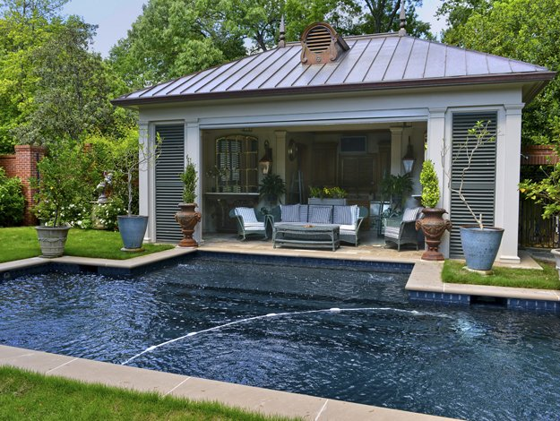 """The pool house with its Southern """"low country"""" architecture, long green shutters, and vintage wicker makes for a shady retreat from summer sun."""