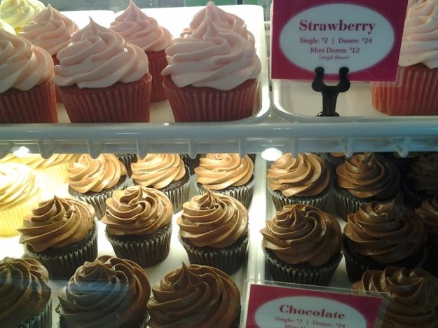 Chocolate and strawberry cupcakes brighten the case at the new Frost Bake Shop in Laurelwood Shopping Center. Diana Nicholas, below, makes the bakery's specialty and wedding cakes.