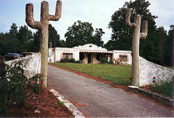 """The """"Spanish House,"""" showing a detail of the garden featuring a lifesize concrete burro and a sombrero-wearing rider."""