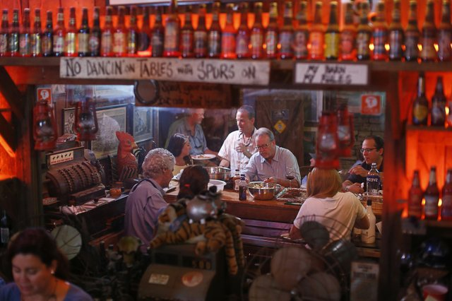 Food, libations, and camaraderie draw folks to the bar as dusk settles over Fat Possum.