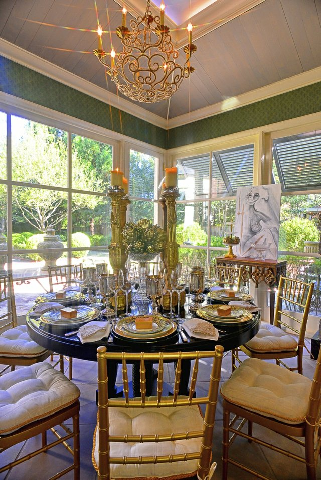The sunroom with its round table, gold chairs, and glorious views of the formal gardens is the perfect setting for a small, elegant family breakfast.