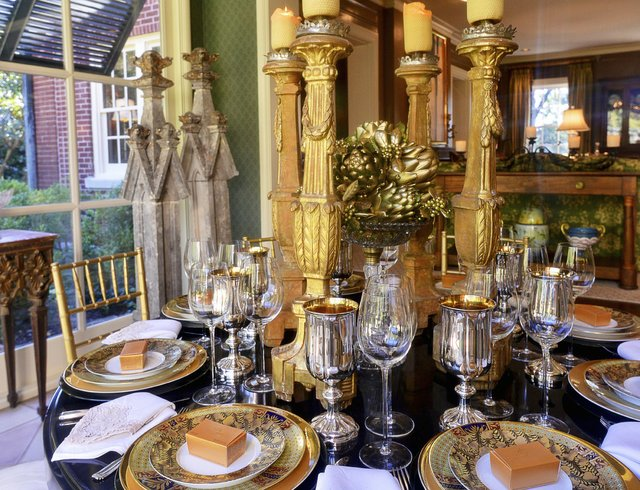 Another angle of the sunroom with its gold-themed place settings, artichoke and holly centerpiece, and tall candlesticks.