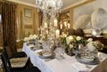 The dining room table is a glistening holiday wonderland with sterling flatware, silvery ruffled china, sparkling crystal, towering white table-top trees, copious candles, and extravagant flowers.