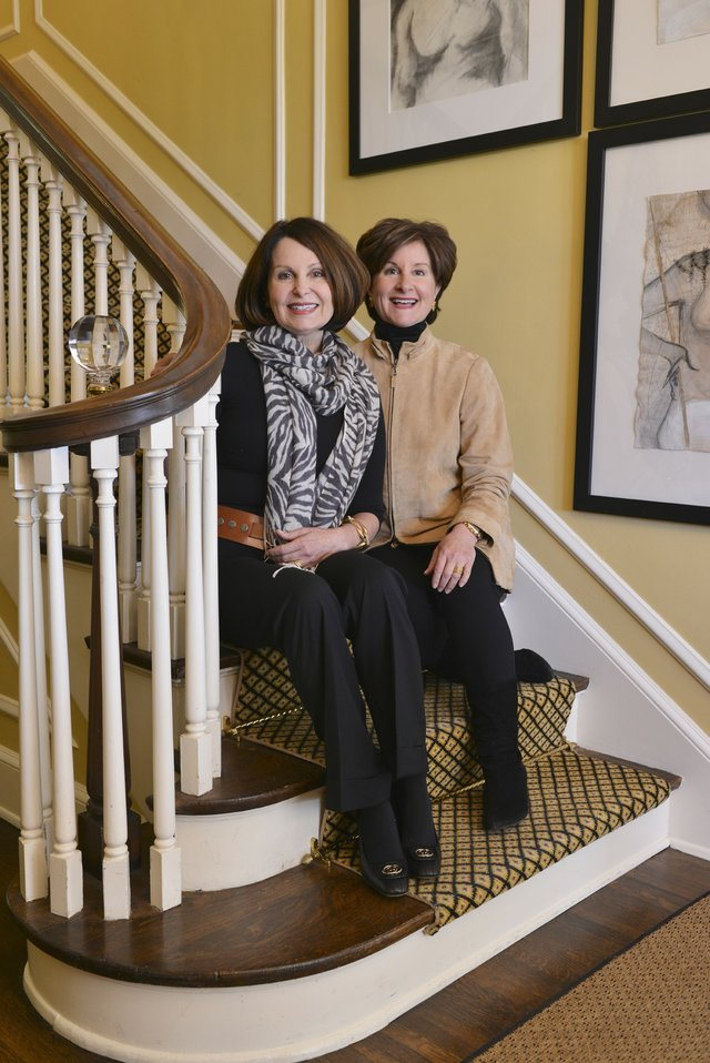 Sisters and business partners Ruthie and Russell pose on the stairs beneath artwork by Bliss Campbell, Ruthie's daughter, who lives in New York City.