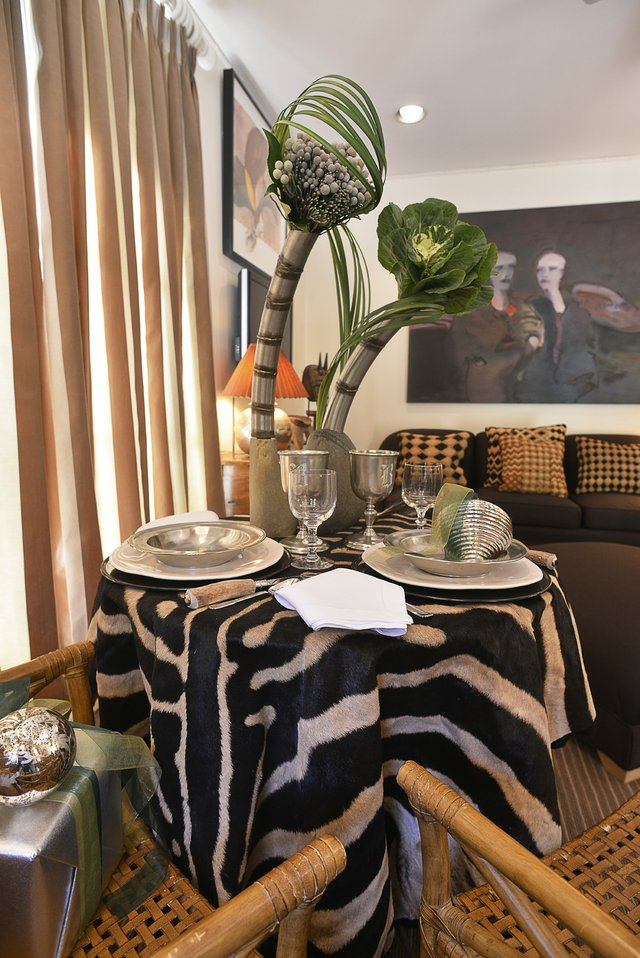 The stunning, very contemporary tablescape in the guest house has an exotic African vibe in keeping with the rattan furniture and zebra rugs.
