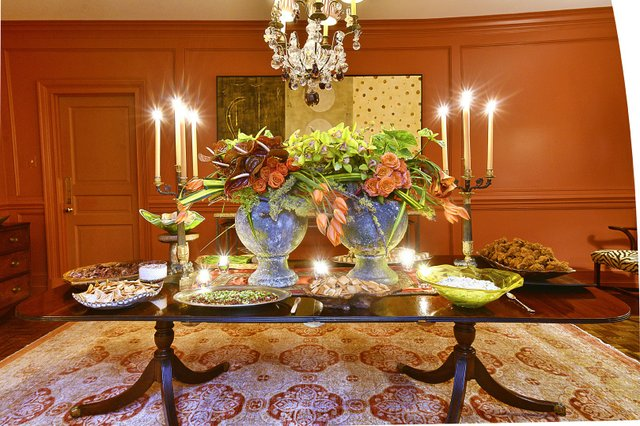 In Russell's dining room two oversize rustic urns brimming with coral-hued flowers make a stunning centerpiece that complements the warm tones of the walls and accentuates the colors in the oriental rug.