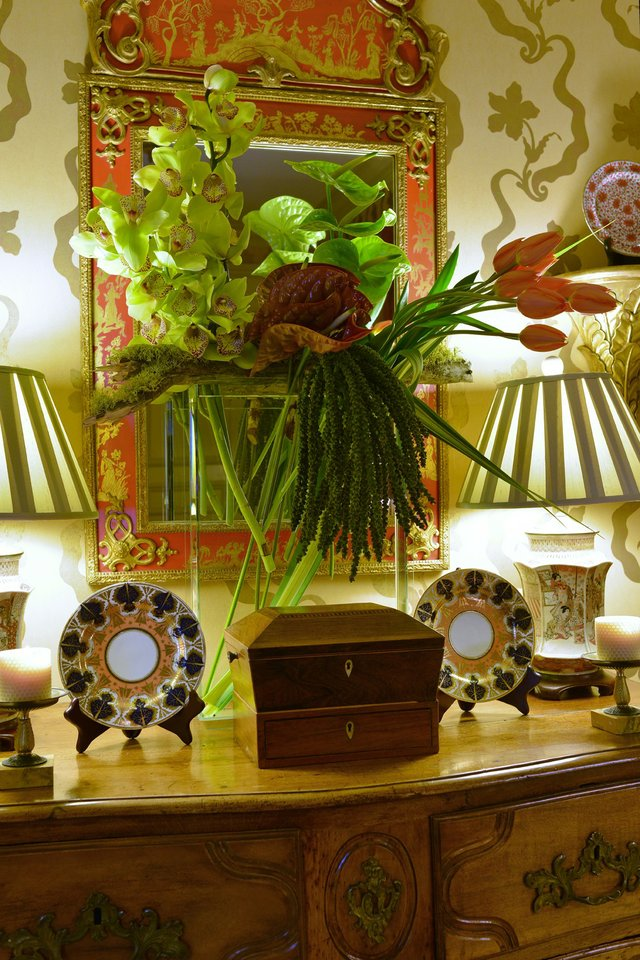 The table-top floral arrangement in the entry of Russell's home is a vivid welcome to visitors, and its colors harmonize with the dining room display.