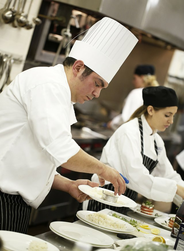 Jose Carias and Erin Burke, of Team Salmon, are among 25 students from the Kemmons Wilson School of Hospitality and Resort Management. Here they prepare the dishes they will present for the judges' approval.