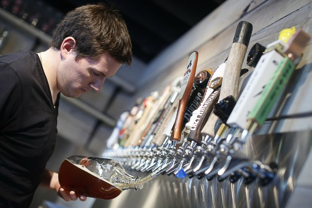 Kevin Eble fills a growler — or small jug — with locally brewed Ghost River beer.