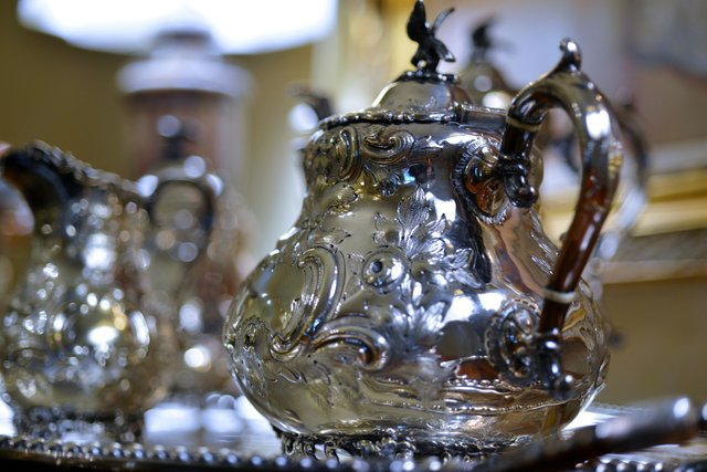 The dining room's antique rococo silver service glistens on the sideboard.