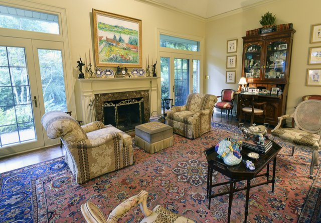 Step down into the living room anchored by a large peach and blue oriental rug, and then step out through French doors to the gracious garden beyond.