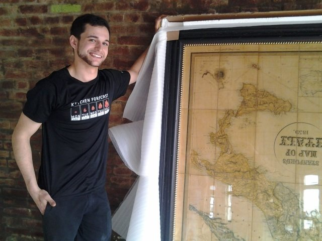 Chef Josh Steiner with a just-unwrapped vintage map of Italy for his new restaurant.
